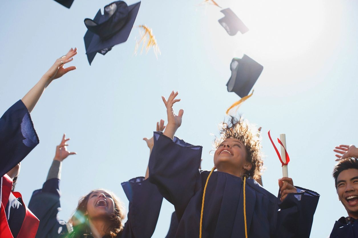 Students throwing their graduation caps to the sky
